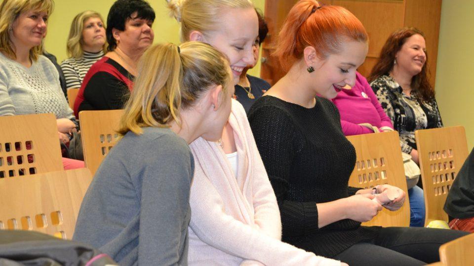 Ženy z publika se snaží najít rakovinné bulky na modelu varlat