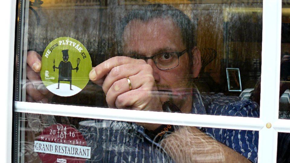Redaktor Tomáš Mařas lepí samolepku Nejsem plýtvák na dveře restaurace