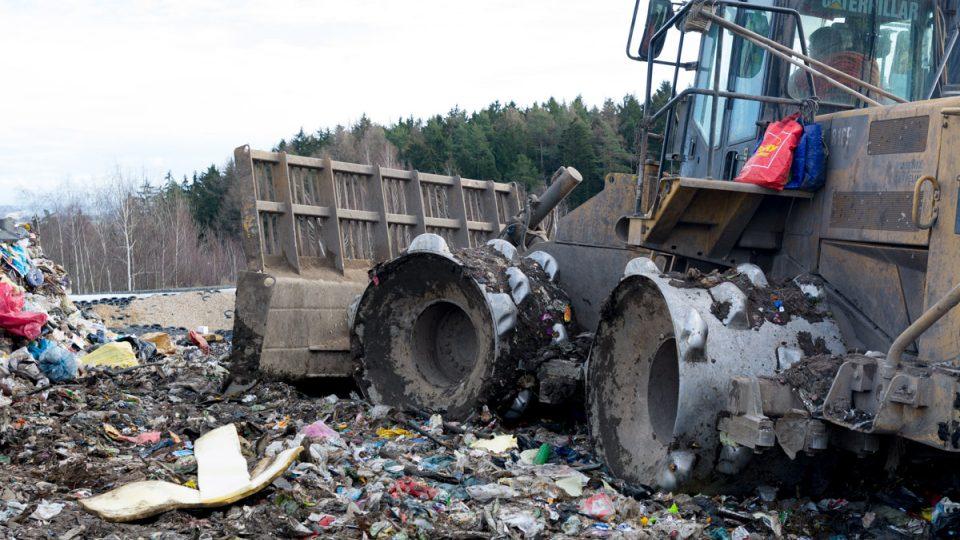 Kompaktor rozhrnuje a udusává odpad na skládce