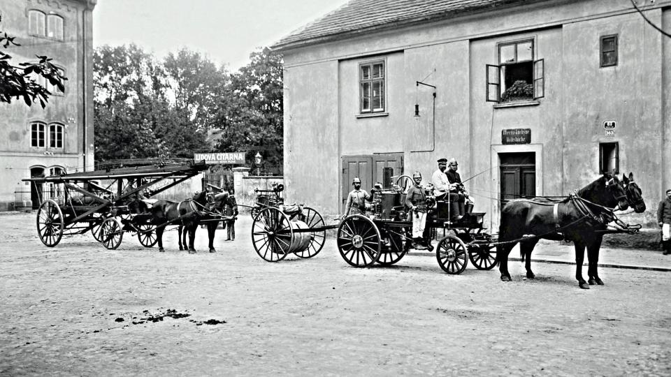 Hasiči s částí vybavení u své stanice v bývalém Panském mlýně (jeho část je patrná při levém okraji snímku) v době kolem roku 1900