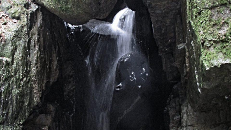 Balvan působí, jako by se pod vodopádem někdo sprchoval