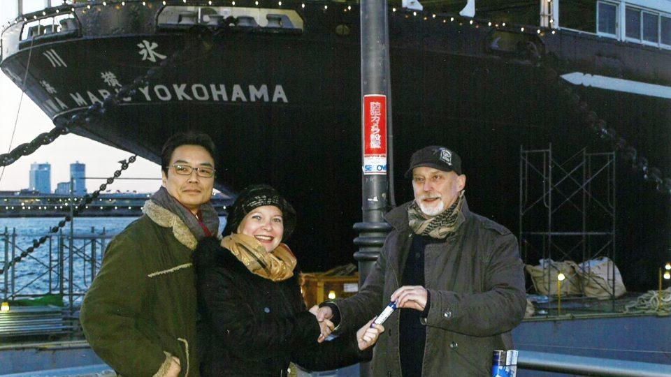 Luboš Hrdlička předává rozhlasovou kešku v přístavu v Yokohamě Adriane Craig a jejímu manželovi
