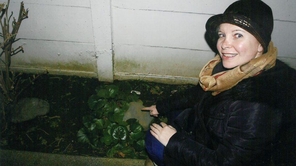 Adriana Craig ukrývá rozhlasou kešku pod kámen