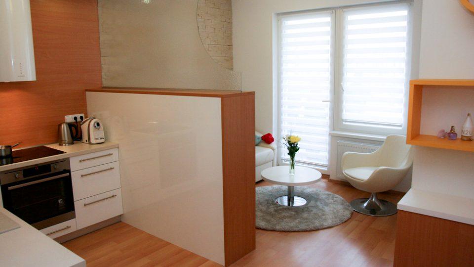 Nižší skříňka a prosklenná stěna decentně vytvoří obývací část