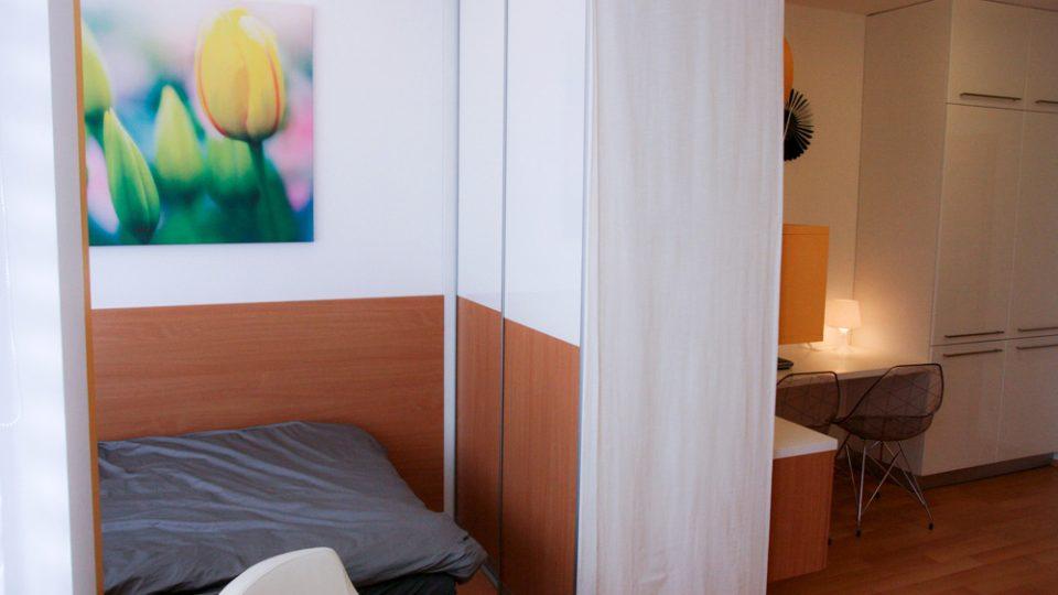 Spací kout vytvoříme oddělením prostorné postele od obývací zóny například pomocí textilních posuvných rolet