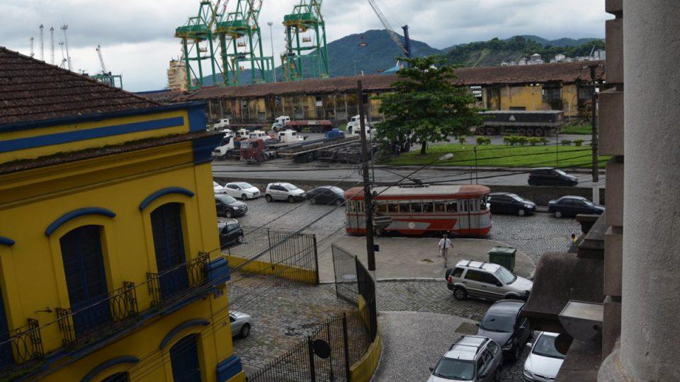 Výhled z balkonu na přístav ve městě Santos. Na ulici jsou vidět projíždějící tramvaje