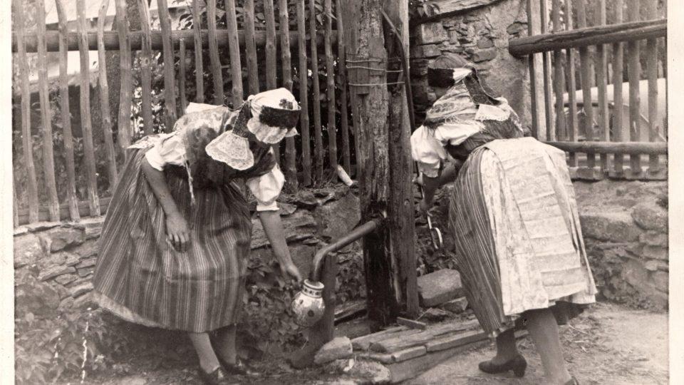 """Žánrová fotografie ženy (s čepcem) a dívky (pouze s """"plenou"""", resp. vínkem) ve stříbrských krojích. Autor neznámý. Sulislav, 30. léta 20. století"""