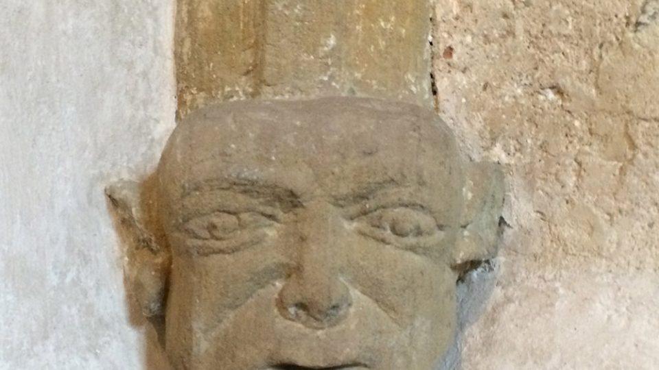 Zakončení žebroví kostela sv. Mikuláše, tahle hlava nevypadá jako cokoli ze 13. století