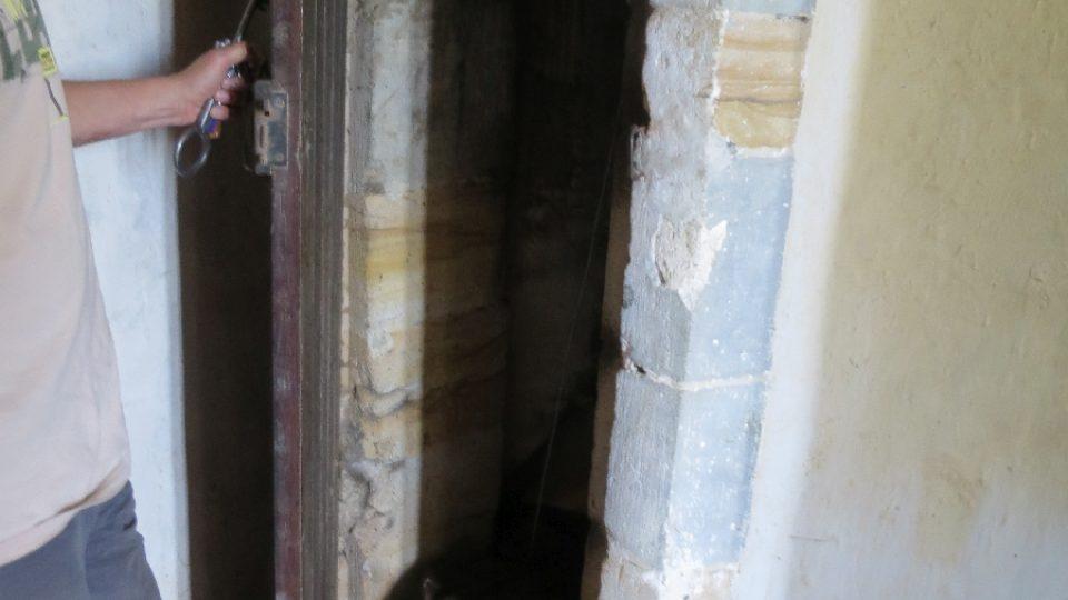 Dveře ke schodišti, kde sídlí netopýři