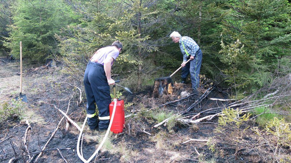 Hasiči Jakub Čiko a Ladislav Košina dohašují požár v lese v místní části Majlant