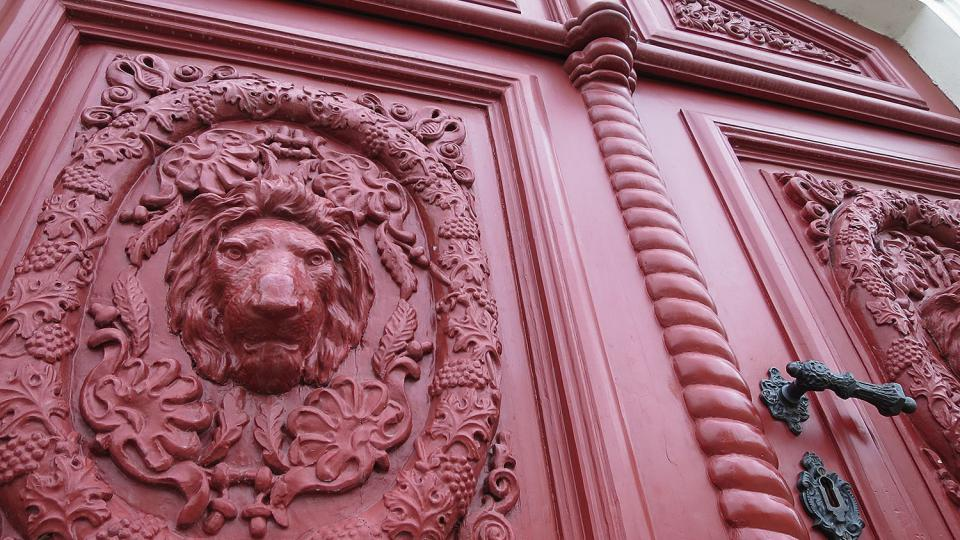 Vrata bývalého hostince čp. 184 na Palackého náměstí, litinové lví hlavy ve věnci z vinných listů a hroznů
