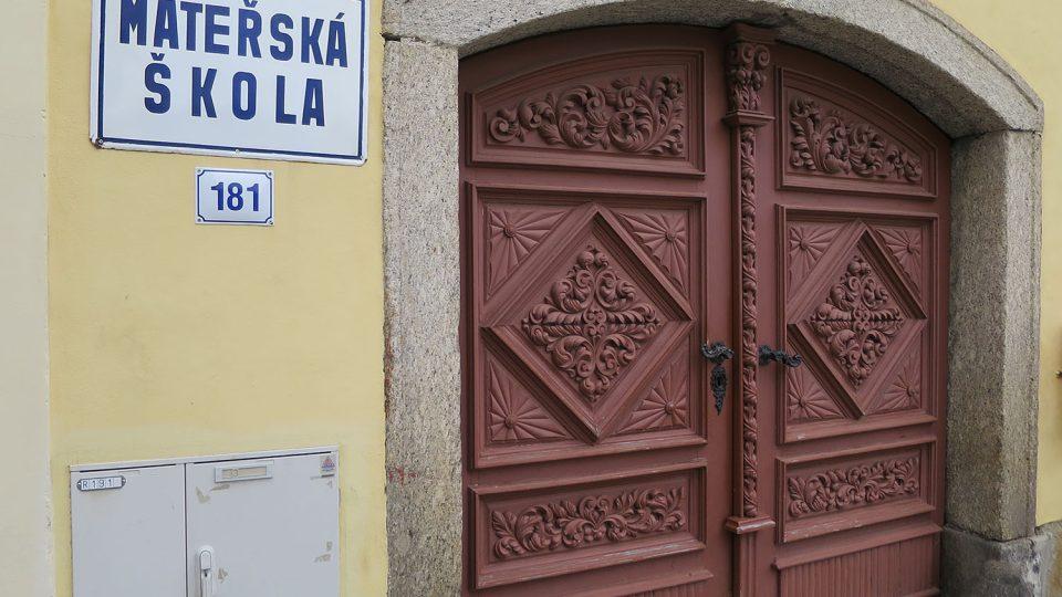 Vrata domu čp. 181 na Palackého náměstí s mimořádně plastickou řezbou