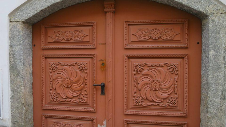 Vrata domu čp. 69 s rotující mnoholistou růžicí, kde se střídají dva typy listů. Fotografie zachycuje zdařilou repliku vrat z roku 1999