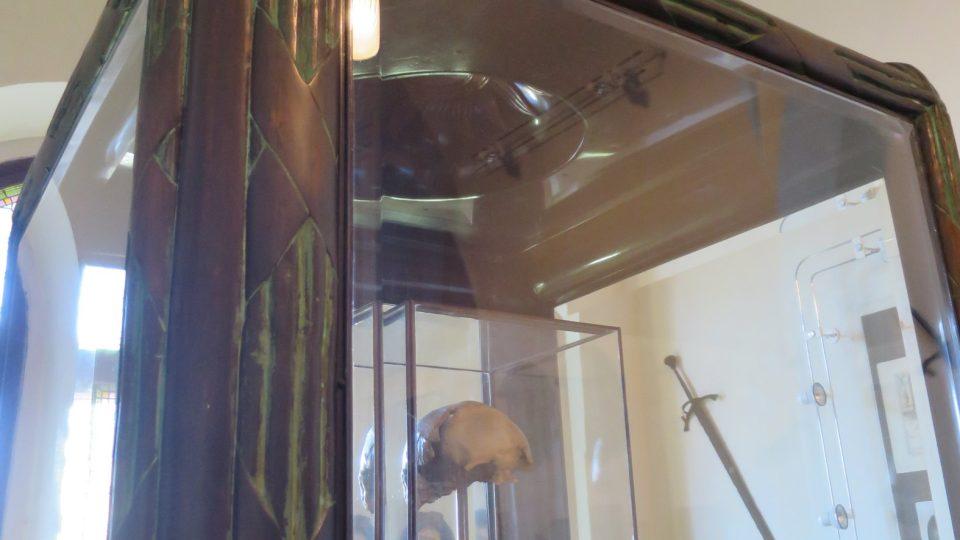 Vitrína je s kubistickými prvky a husitským pohárem jako symbolem husitů