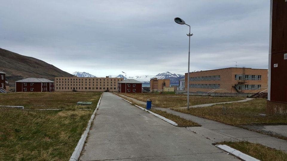 V pozadí za domy ledovec Nordenskiold v zátoce Billefjorden Barentsova moře