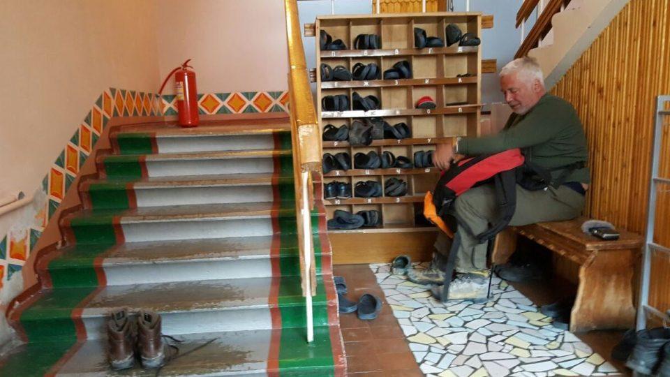 Parazitolog Oleg Ditrich si zouvá boty před vstupem do baru v bývalé hornické osadě Pyramiden na Svalbardu