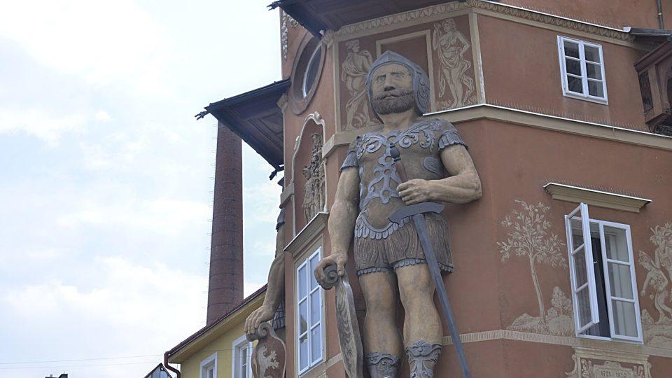 V průčelí věže stojí postavy dvou obrů, rolandů, v římské zbroji