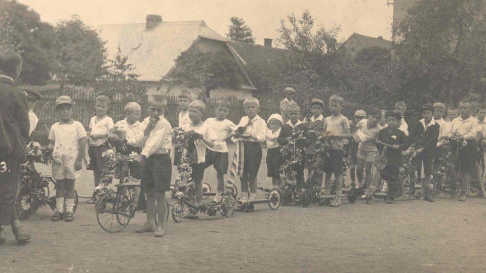 František Wiendl (v tmavém na koloběžce - druhý z prava), 30. léta, školní průvod, Voříškova ulice v Klatovech