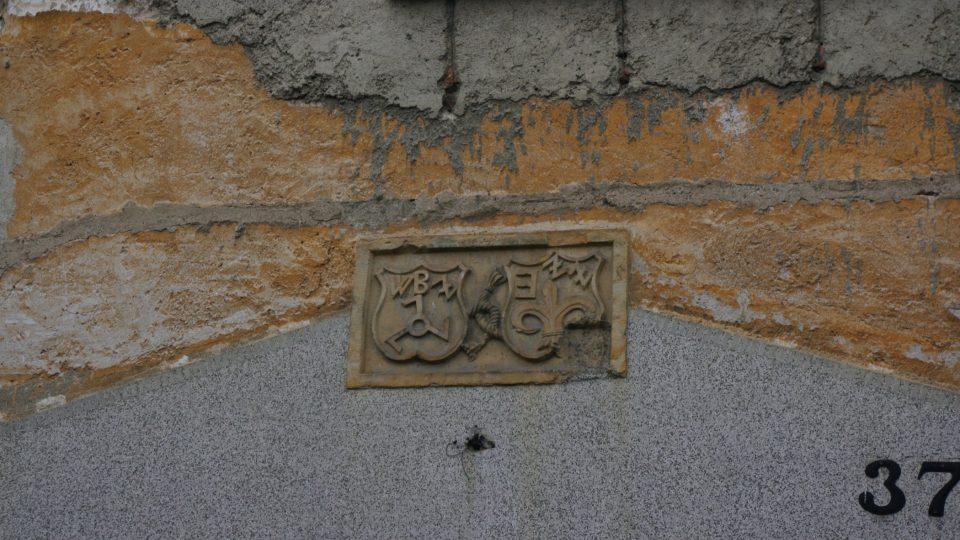 Částečně zachovalé erby nad vstupem do zámku