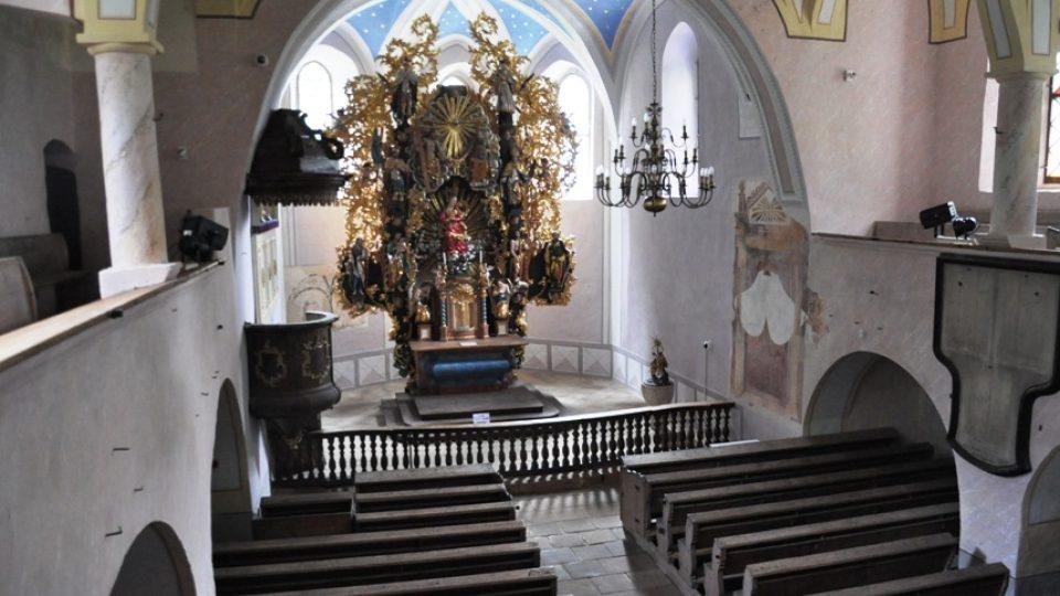 Interiér starého kostela je lutheránsky strohý, ale zdobí ho zlatý barokní oltář