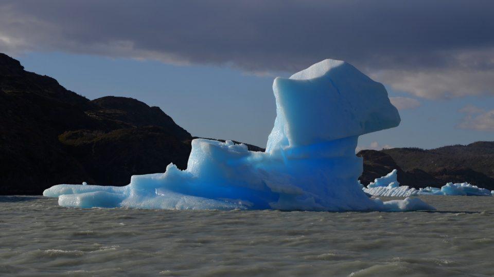 Kontrasty. Jezero je plné šedé neživé vody. Ledovce blankytně modré