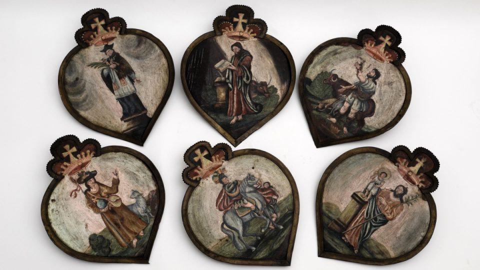 Soubor šesti barokních pohřebních štítů s vyobrazeními sv. Martina, sv. Josefa, sv. Jana Nepomuckého, sv. Lukáše, sv. Notburgy a sv. Rocha. Lidová práce z poloviny 18. století