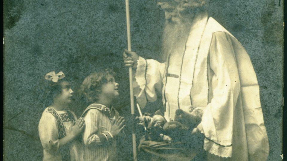 """Černobílá fotografie upravená na pohlednici s nápisem """"Pozdrav od Mikuláše"""". Datace počátek 20. století"""