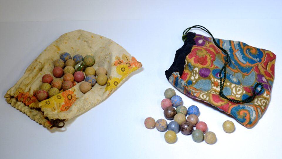 """Dva pytlíky s hliněnými barvenými kuličkami (tzv. """"hliněnkami"""") ze 40. let 20. století"""
