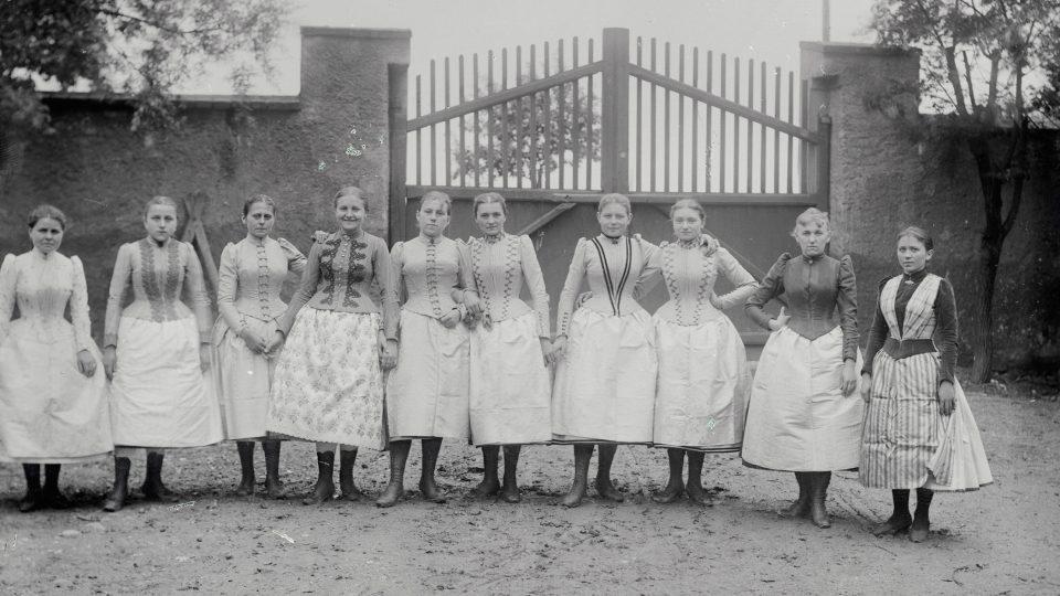 """Skupina venkovských dívek, Adolf Kopecký, kolem 1900. Ačkoli původní popiska k fotografii zní """"skupina dívek v plzeňském kroji"""", jejich oděv je již výrazně ovlivněn soudobou městskou módou"""