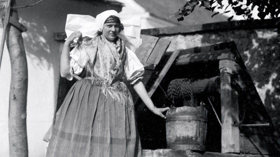 Děvče z Druztové v kroji u studny. Nedatovaný snímek pochází nejspíš z první třetiny 20. století a působí již trochu naaranžovaným dojmem
