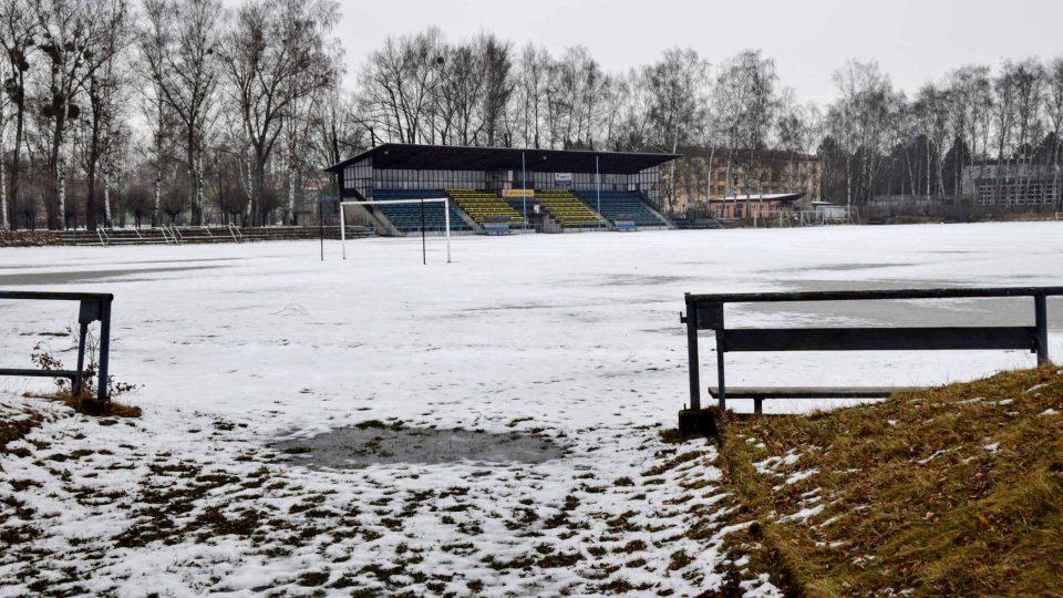 Travnaté hřiště s atletickým oválem pod sněhem