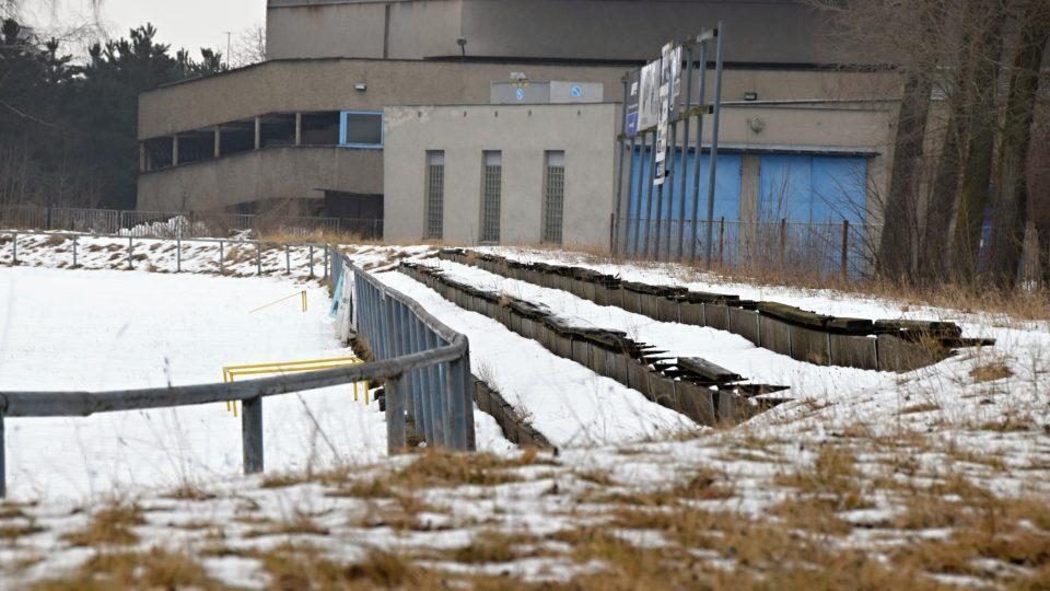 Zbytky laviček pro diváky u fotbalového hřiště