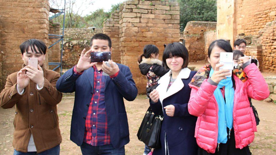 Čínští turisté si spíše než historické ruiny fotí jejich současné obyvatele - čápy