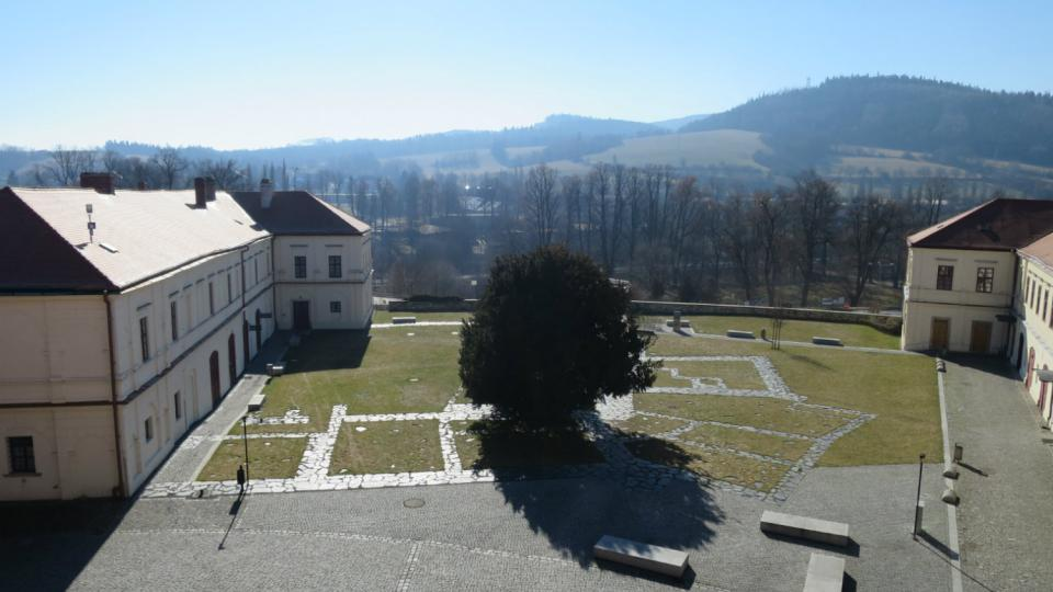 Pohled z arkád na zámecké nádvoří, kde je vyznačený půdorys původního hradu