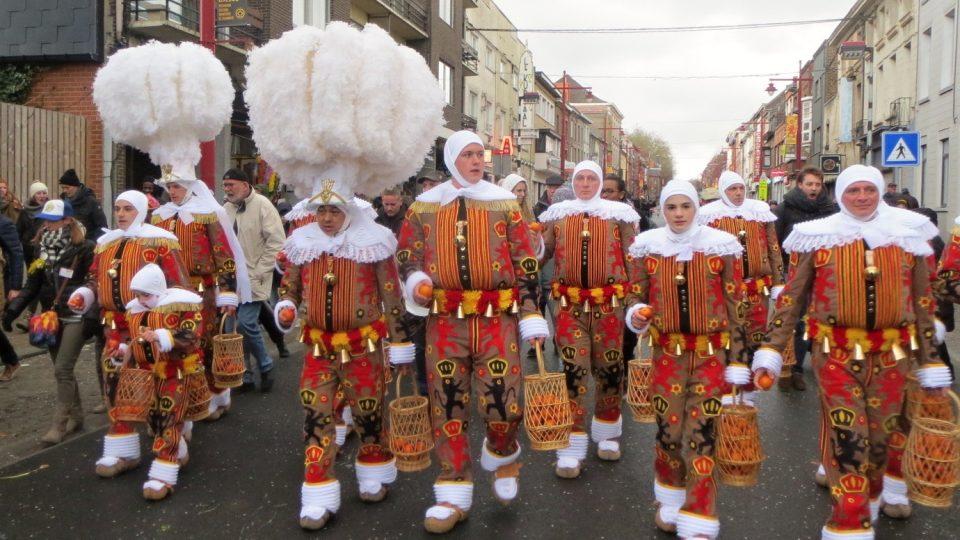 Gillové pochodují v kostýmech v národních barvách a velkých kloboucích s bílými pery
