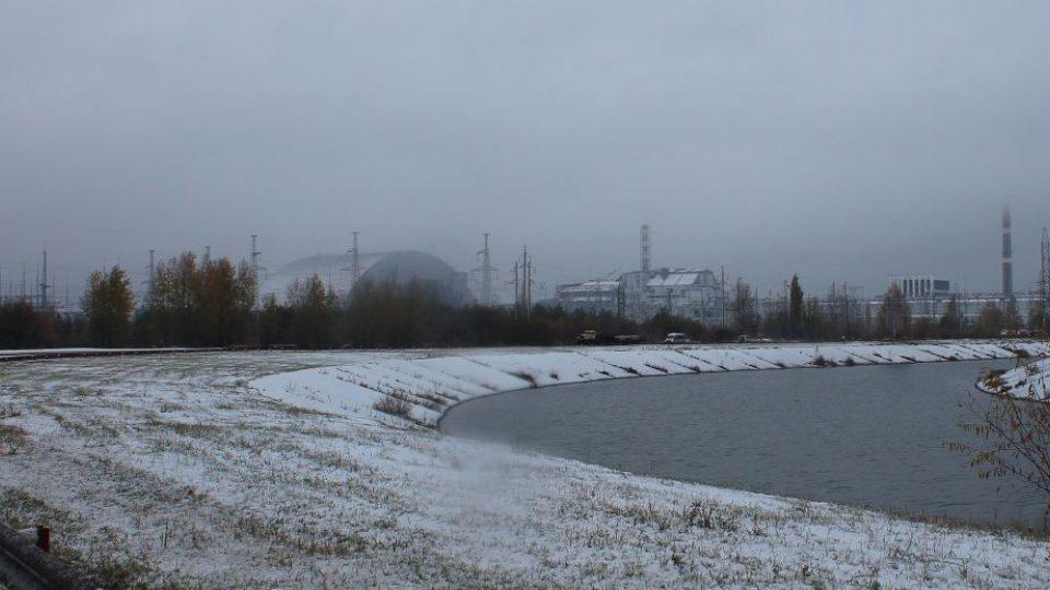 Pohled na černobylskou jadernou elektrárnu - vlevo monstrózní nový sarkofág, uprostřed havarovaný 4. blok (nalevo od komína) a 3. blok, vpravo - vyšší čtvercové budovy s bílými komíny jsou 1. a 2. blok