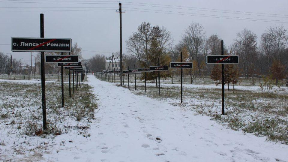 Alej zaniklých obcí v Černobylu. Každou opuštěnou vesnici či město zastupuje v tomto památníku jedna cedule