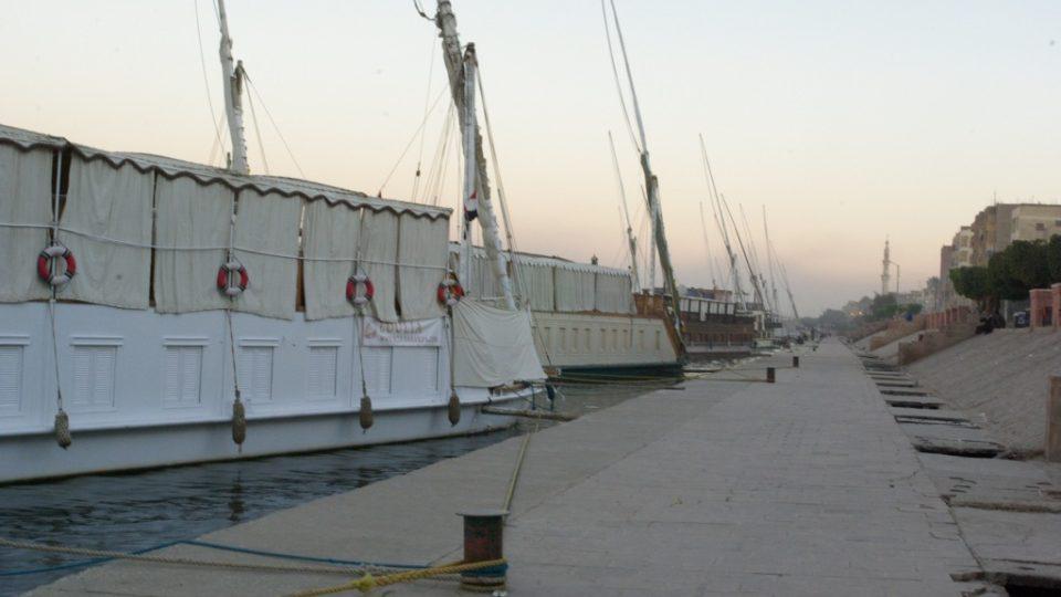 Cestující si prohlížejí památky a zajímavosti na břehu a jejich loď v přístavišti čeká, až se znovu nalodí
