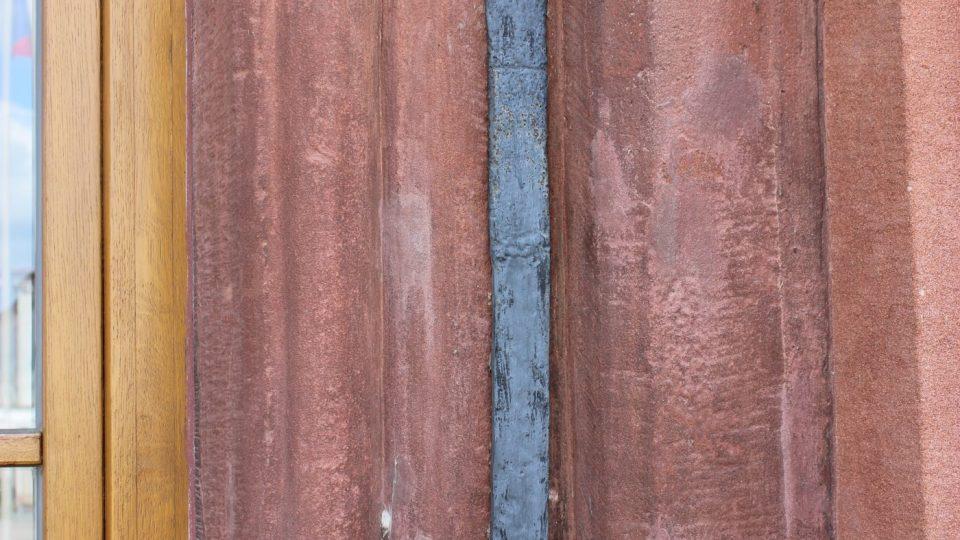 Moravský loket je zazděný v kamenném ostění vstupu do radnice