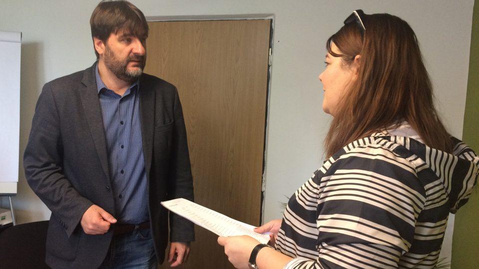 Předsedkyně kolejní rady Moniky Ryšlinková předává řediteli SKM Tomáši Krausovi petici proti propouštění vrátných.JPG