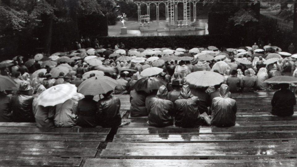 Dnes už se diváci pod deštníky choulit nemusí, tak jako na představení Dvě vdovy v roce 1962