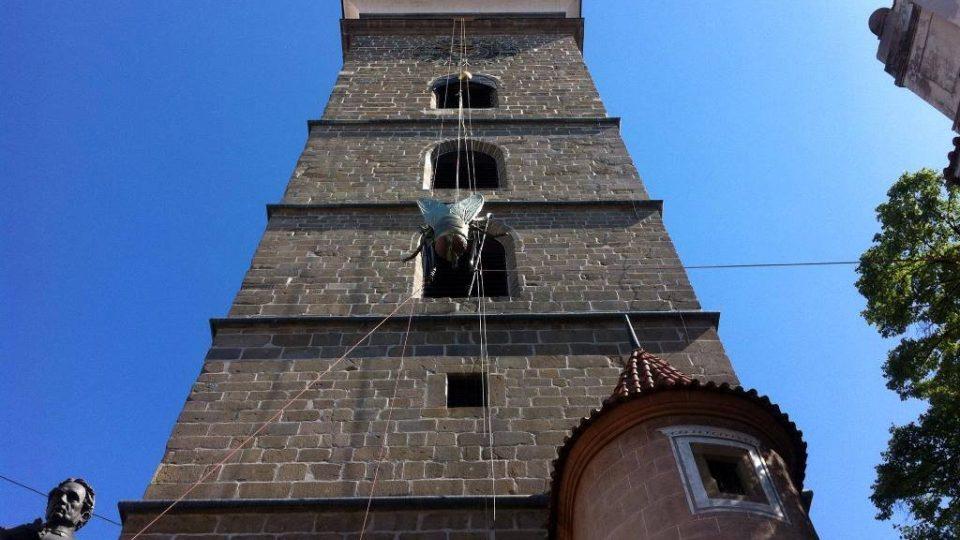 Připevňování obří mouchy Michala Trpáka do prostředního okna Černé věže v Českých Budějovicích