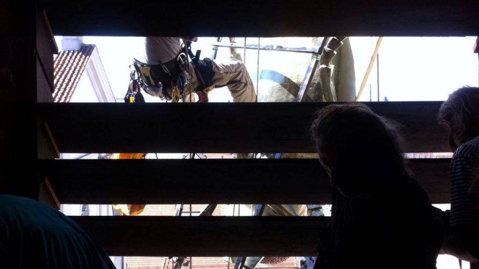 Připevňování obří mouchy Michata Trpáka do prostředního okna Černé věže v Českých Budějovicích