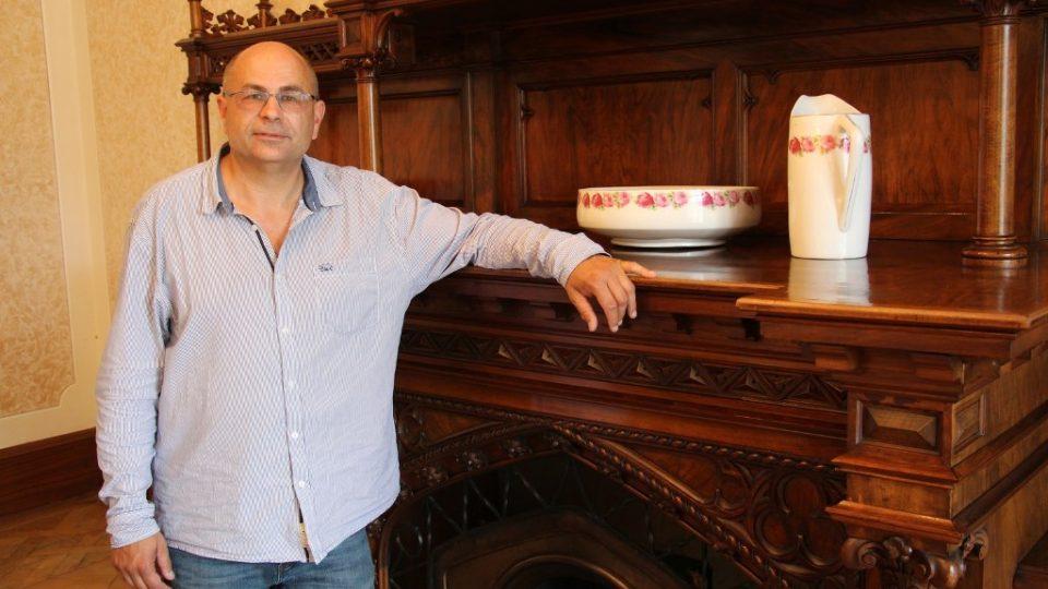 Ředitel lázní ve Vráži Jiří Landa u unikátního dřevěného krbu