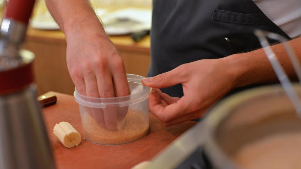 Nakrájejte oloupaný banán na malé špalíčky, které ještě překrojte podélně. Stranu řezu otiskněte ve vrstvě třtinového cukru
