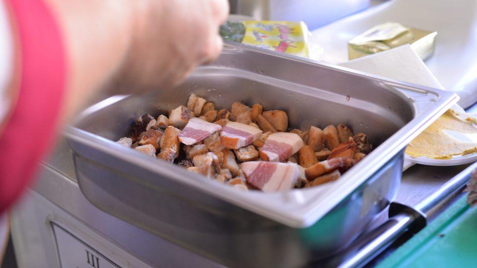 Přidáme nahrubo nakrájenou cibuli, kmín, petrželku, může být i trocha česneku, přiložíme kousky slaniny