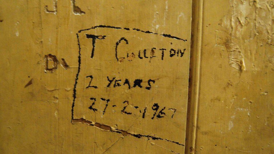 Vzkazy na stěnách a dveřích dodnes připomínají dávné obyvatele policejních cel