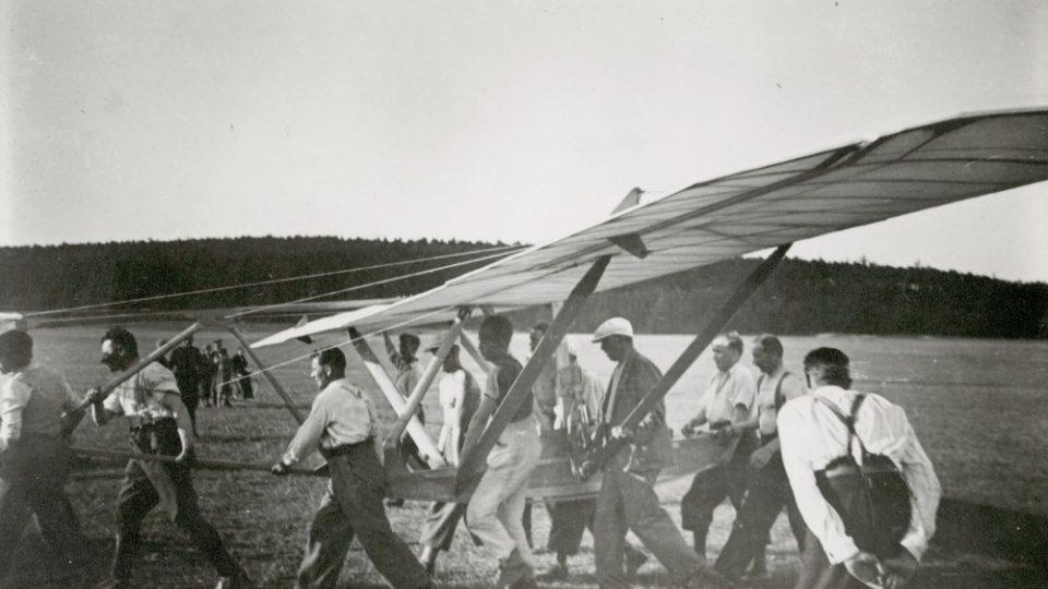 Kluzák Skaut vyráběný v dílnách MLL u firmy Sodomka nesou letuchtivý zájemci na start, aby se jeden z nich dostal alespoň na chvilku do vzduchu. 2. polovina 30. let, letiště Vysoké Mýto. Ze sbírek Regionálního muzea ve Vysokém Mýtě