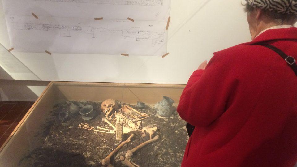 Ukázka hrobu s keramickými milodary a bronzovými šperky. Žena zemřela zhruba dva tisíce let před naším letopočtem