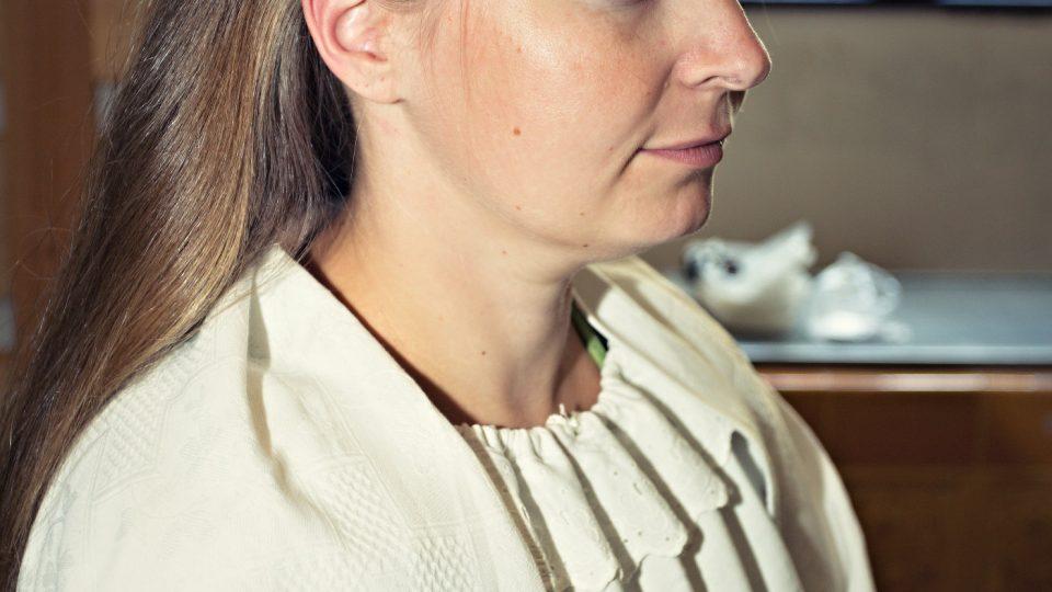 Fotografie znázorňuje rozdělení vlasů na pěšinku a vytvoření klapek